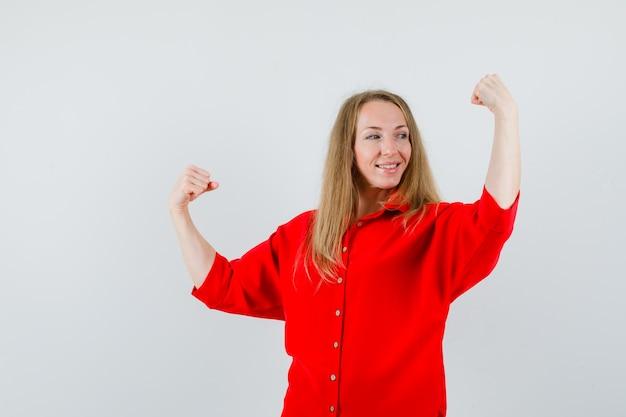 赤いシャツで勝者のジェスチャーを示し、自信を持って見える女性。