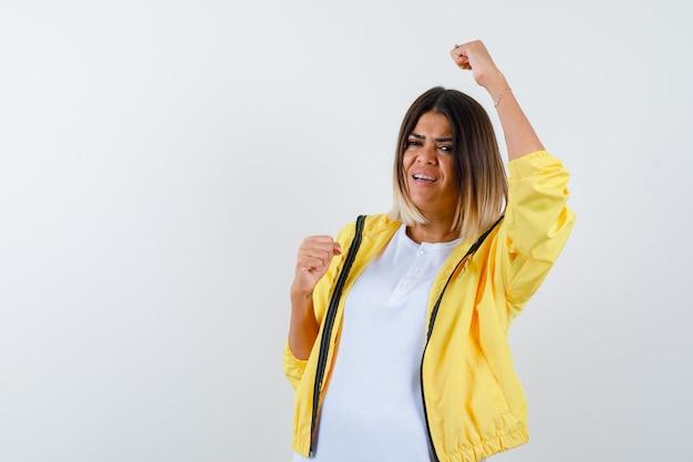 Tシャツ、ジャケット、幸運な、正面図で勝者のジェスチャーを示す女性。