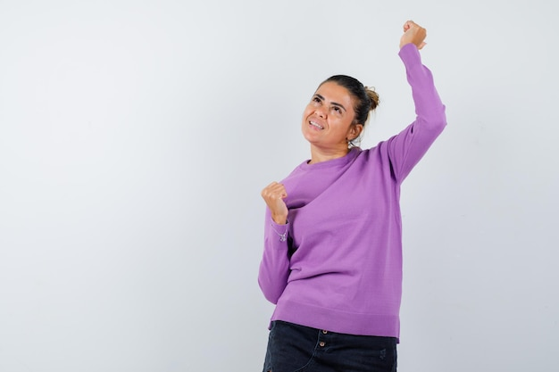 ウールのブラウスで勝者のジェスチャーを示し、幸運に見える女性
