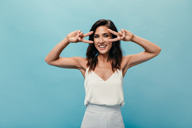 Lady in silk top shows peace signs on blue background