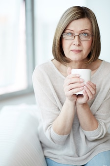 Lady sitting on the couch with a cup of coffee