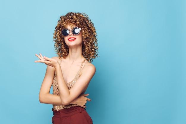 Lady smile curly hair gesture hands studio dark glasses brown pants cropped view