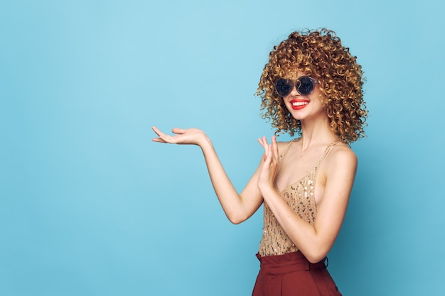 Lady smile curly hair red lips gesture with hands copy space red pants blue isolated background