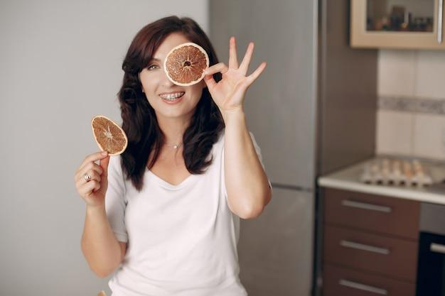 女性はカメラに微笑みかけます。製菓業者は台所で料理をします。クックは休んでいます。