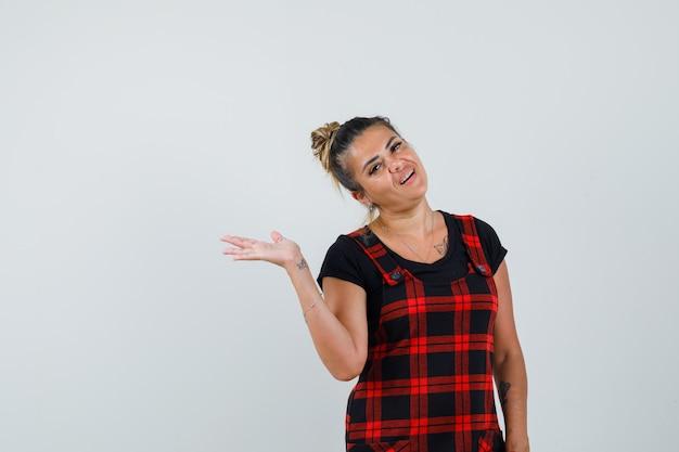 ピナフォアのドレスを着て手のひらを広げ、自信を持って見える女性。正面図。