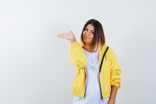 레이디 티셔츠, 재킷에 손바닥을 옆으로 펼치고 자랑스럽고 전면보기.