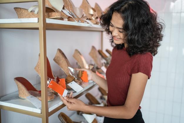 Леди стоя в бутике магазина обуви в помещении