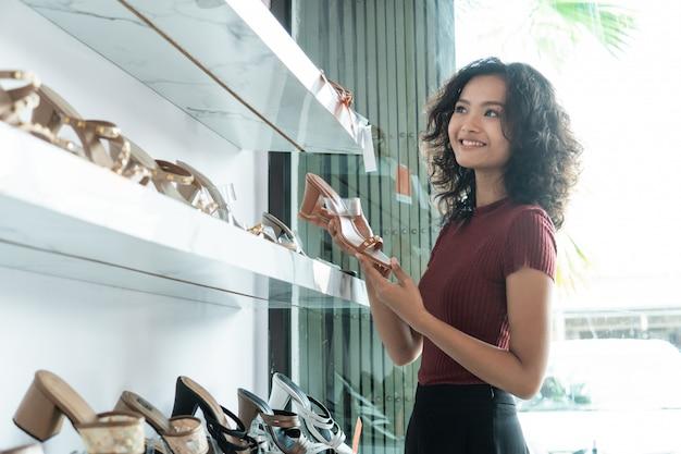 Леди стоя в бутике обувного магазина
