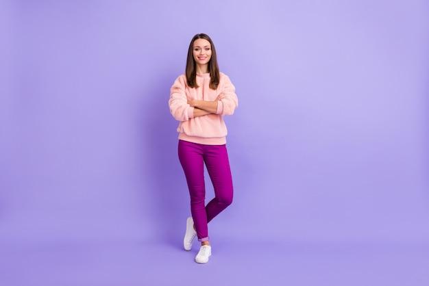Леди, стоящая на фиолетовом фоне со скрещенными руками