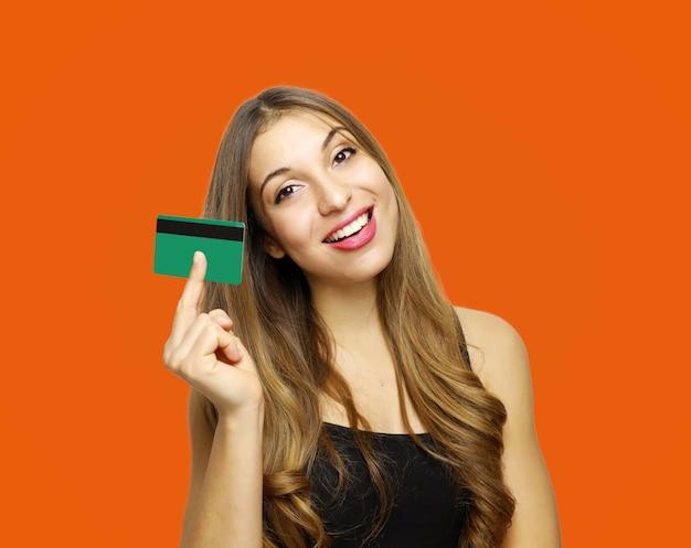 Леди стоит над оранжевой стеной и держит в руках дебетовую карту