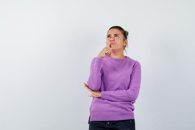 Signora in piedi in posa pensante in camicetta di lana e con un aspetto sognante