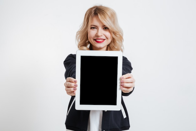 Lady standing over white background showing display of tablet