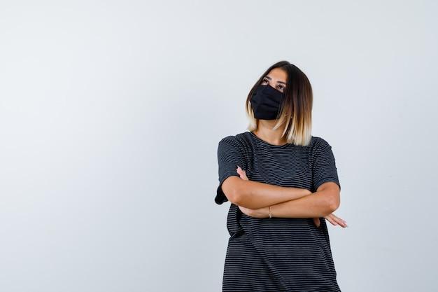 Signora in piedi con le braccia incrociate in abito nero, maschera medica e sembra speranzosa. vista frontale.