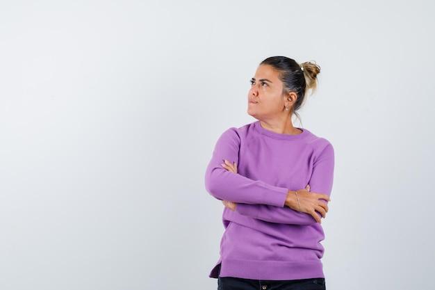 Дама стоит со скрещенными руками в шерстяной блузке и задумчиво смотрит