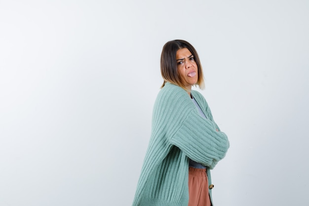 腕を組んで立っている女性、カジュアルな服装で舌を突き出し、意地悪に見える女性。 。