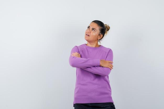 Signora in piedi con le braccia incrociate in camicetta di lana e guardando pensierosa