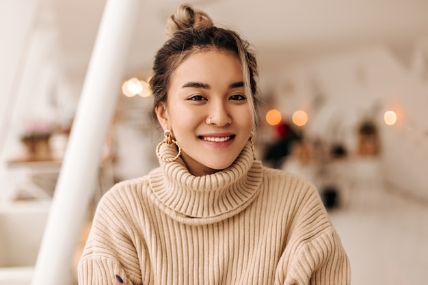 Lady in stylish beige oversize sweater looks into front