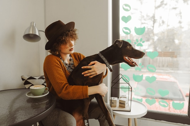 Lady in stylish clothes playing with a dog in a cozy coffee shop by the window