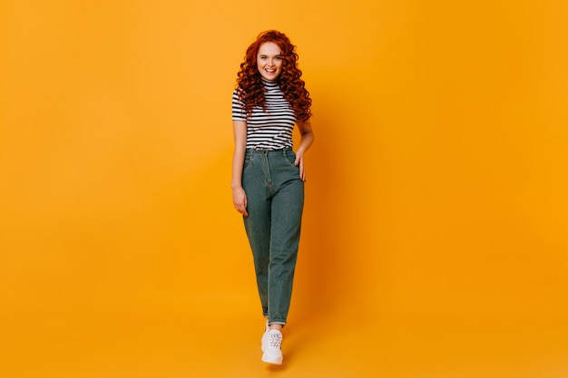 Lady in stylish denim pants and striped top posing on orange space. full-length shot of redhead girl.