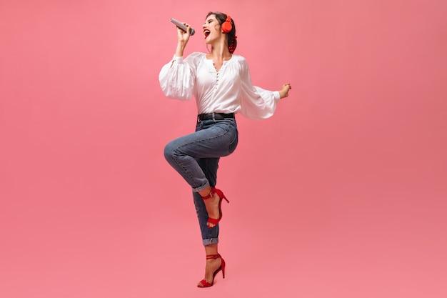 Lady in stylish outfit emotionally sings in microphone on pink background.  beautiful young woman in red headphone posing.