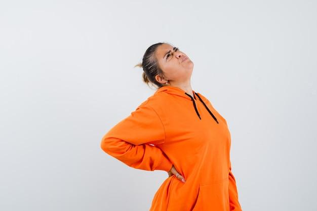Signora che soffre di mal di schiena in felpa con cappuccio arancione e sembra affaticata