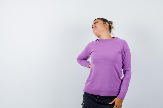 Signora che soffre di mal di schiena in camicetta di lana e sembra stanca