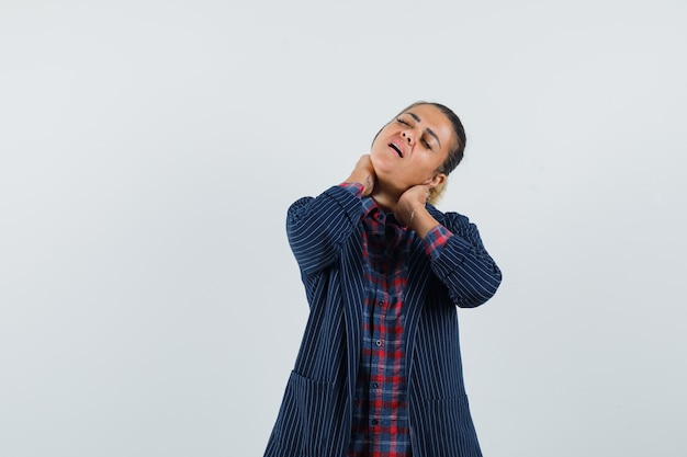 Дама страдает от боли в шее в рубашке, куртке и выглядит утомленной. передний план.