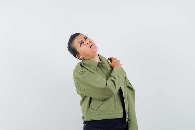 Lady suffering from shoulder pain in jacket