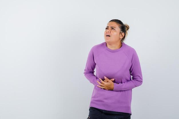 Signora che soffre di mal di stomaco in camicetta di lana e sembra a disagio
