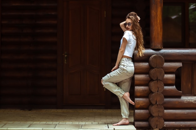 Lady in sunglasses at the wooden house posing