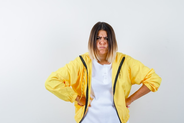 Lady in t-shirt, jacket keeping hands on waist and looking spiteful , front view.