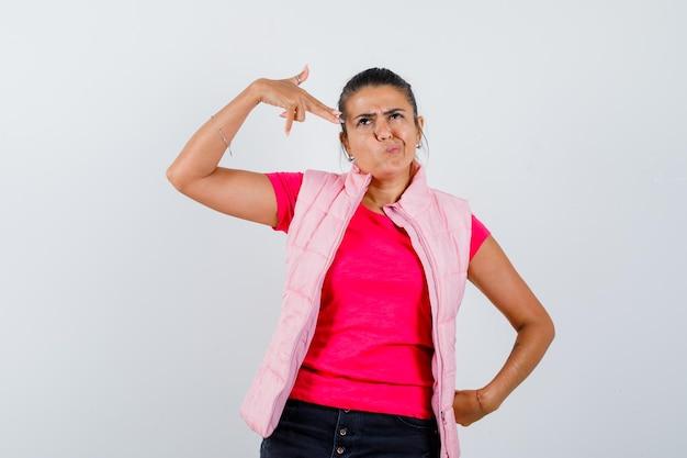 Signora in t-shirt, gilet che fa un gesto suicida e sembra esitante