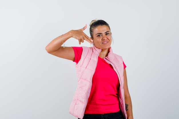 Lady in t-shirt, vest pointing at herself and looking proud