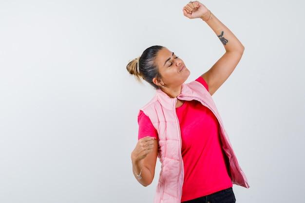 Signora in t-shirt, gilet che mostra il gesto del vincitore e sembra felice