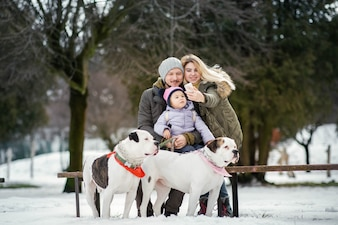 Lady takes a selfie posing with her man and daughter with two American bulldogs