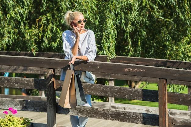 Lady talking onsmartphone on footbridge