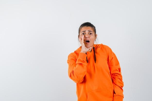 Дама в оранжевой толстовке с капюшоном рассказывает секрет с рукой возле рта и выглядит встревоженной
