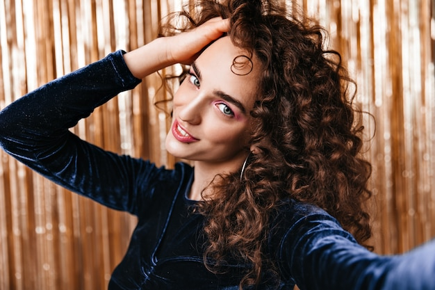 Lady touches her curly hair and taking selfie on gold background