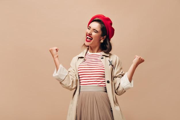Signora in trincea alla moda e cappello in posa emotivamente su sfondo beige. felice giovane donna con i capelli scuri in berretto rosso esulta.