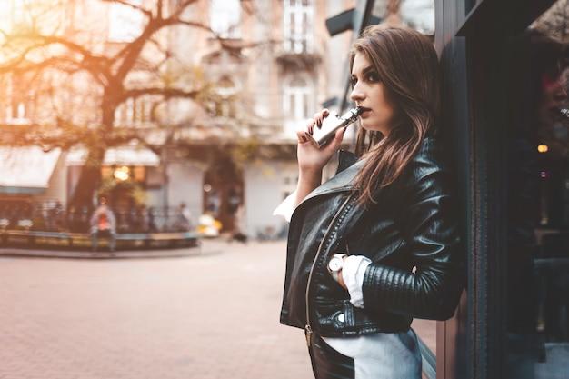 Леди использует электронную сигарету на городской улице