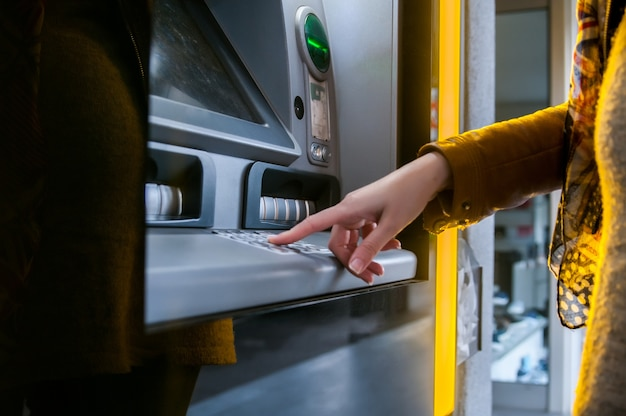 Lady using atm machine to withdraw her money.