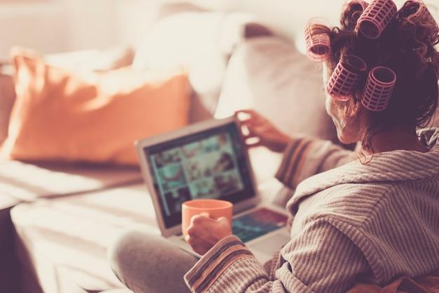 Женщина смотрит со спины, используя современный ноутбук дома, в то время как бигуди на его вьющихся волосах