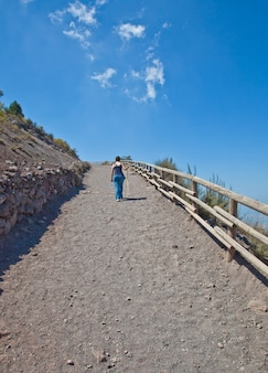 Lady walking for exercises during a sunny day on a mountain path