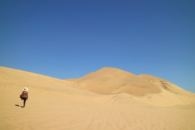 Lady walking on the incredible sand dunes of huacachina desert in ica region of peru, south america