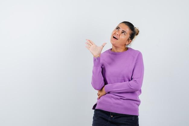 Signora agitando la mano per dire addio in camicetta di lana e guardando allegra