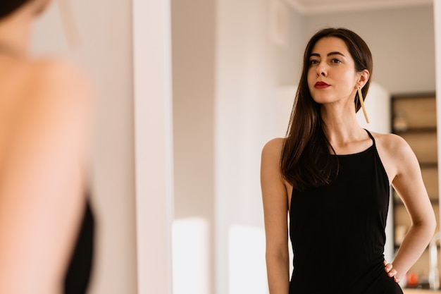 Lady wears beautiful black dress looking into the mirror