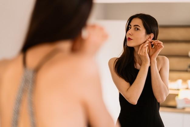 女性は鏡を見る美しい黒のドレスを着ています。