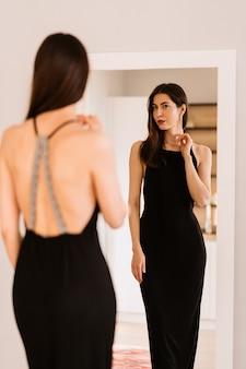 Леди носит красивое черное платье, глядя в зеркало