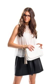 Леди носит блузку со вставкой. белый топ и сумочка. привлекательная девушка в очках. вечерняя одежда на лето.