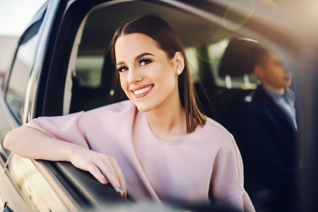 Lady well dressed with toothy smile leaning on car window and looking at camera while her boyfriend driving.